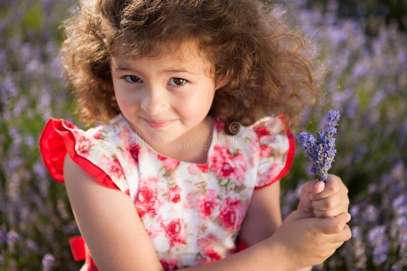 Menina feliz bonita com o ramalhete de flores do verão no campo da alfazema imagens de stock royalty free