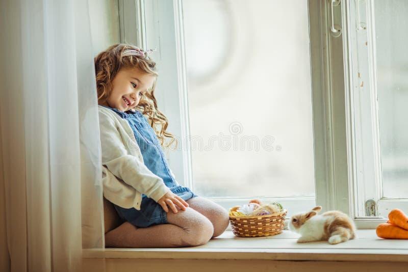 A menina feliz bonita da criança está sentando-se no peitoril com seu coelho colorido pequeno do amigo, conceito da janela do fer imagem de stock