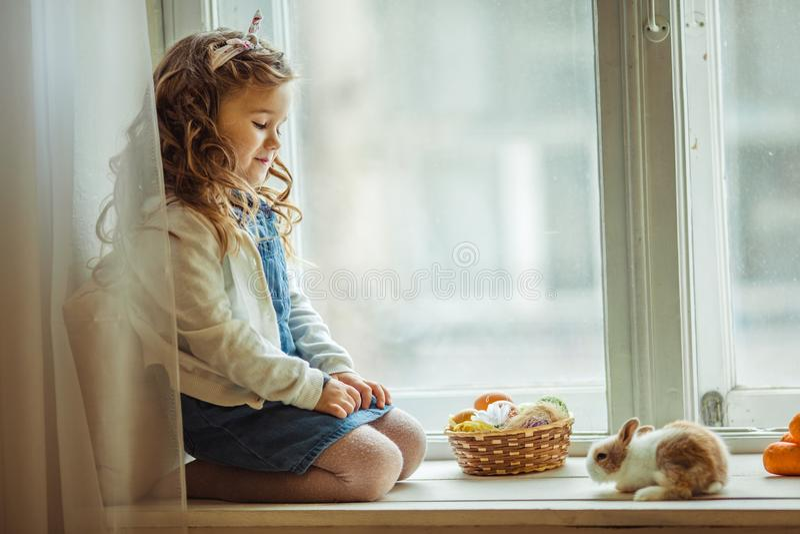 A menina feliz bonita da criança está sentando-se no peitoril com seu coelho colorido pequeno do amigo, conceito da janela do fer fotografia de stock royalty free