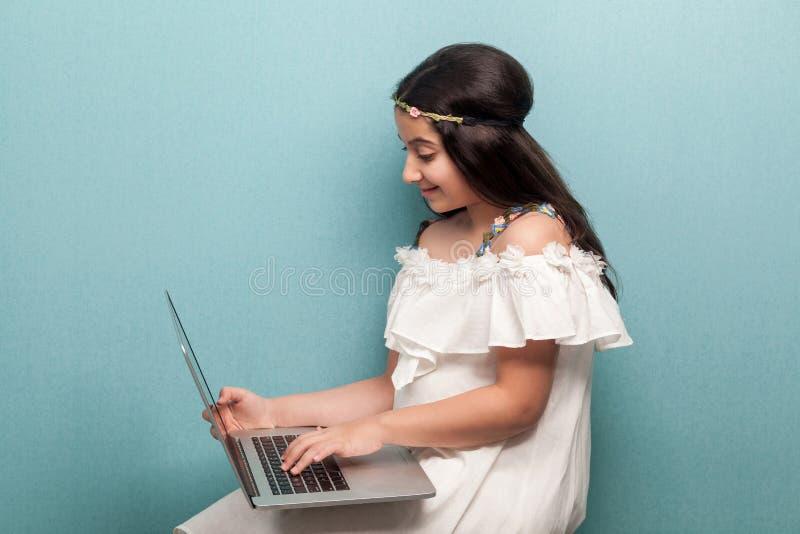 Menina feliz bonita do adolescente com cabelo preto longo no vestido branco que senta e que usa seu port?til olhando a exposi??o  imagens de stock royalty free
