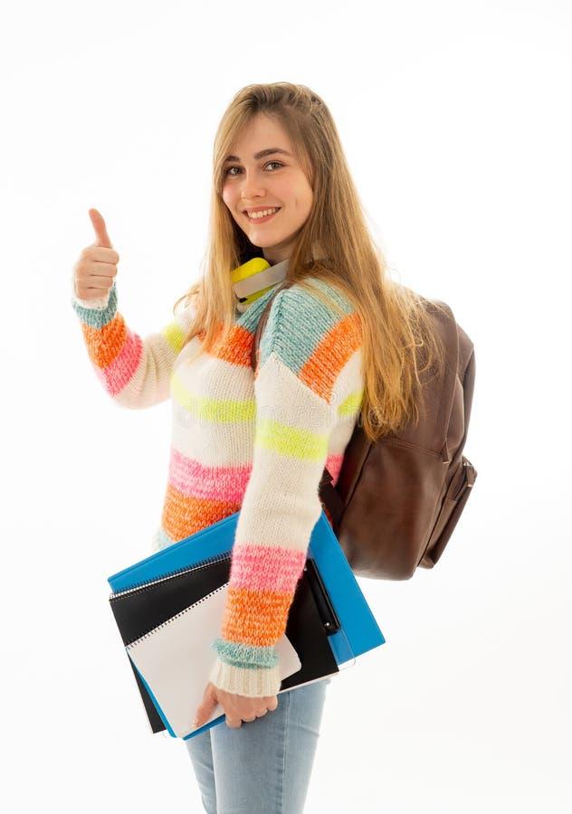 Menina feliz bonita do estudante do adolescente que mostra os polegares acima imagem de stock royalty free