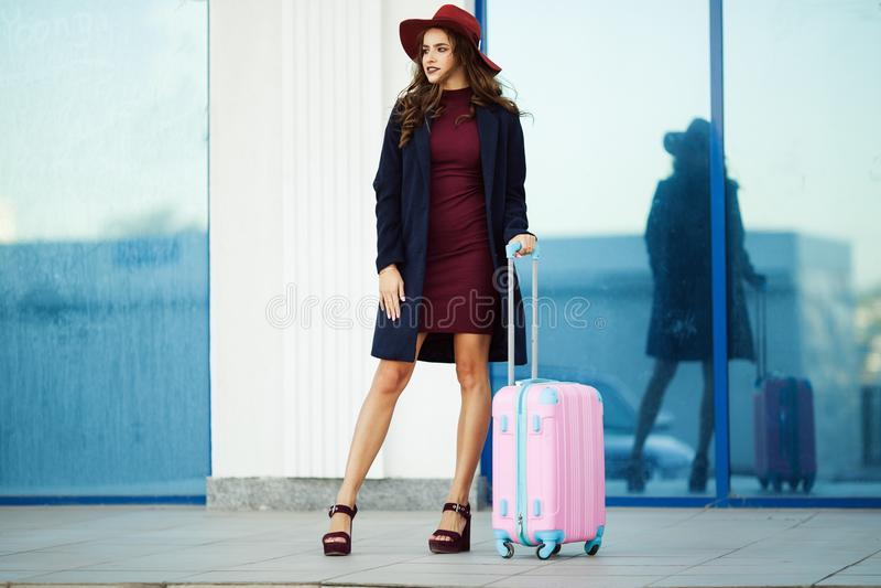 A menina feliz bonita está vestindo a roupa e o chapéu da forma perto do aeroporto com mala de viagem cor-de-rosa Foto do conceit foto de stock royalty free