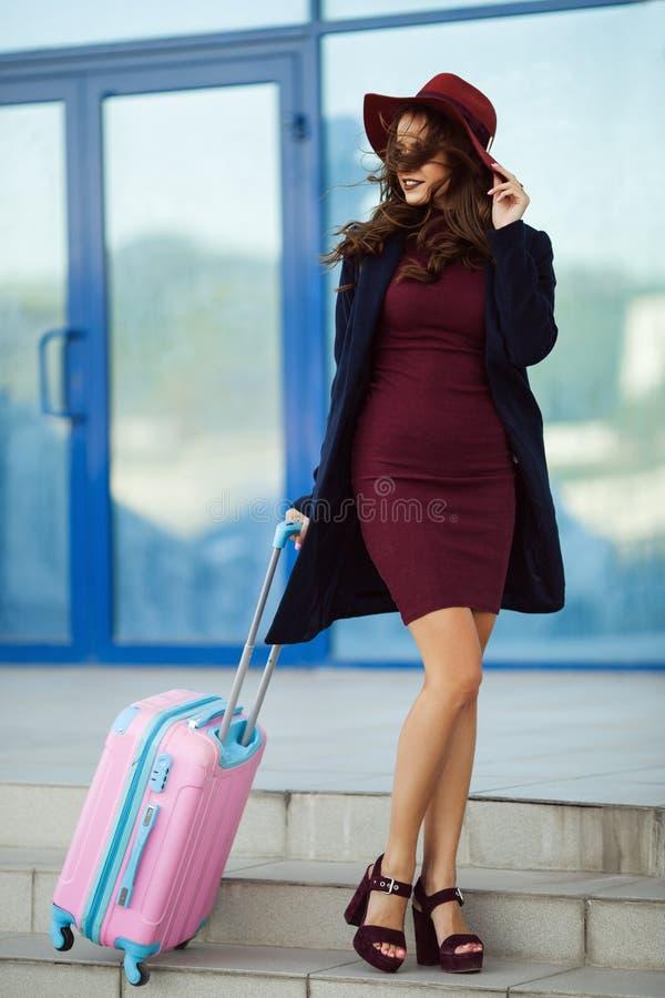 A menina feliz bonita está vestindo a roupa e o chapéu da forma perto do aeroporto com mala de viagem cor-de-rosa Foto do conceit fotografia de stock royalty free