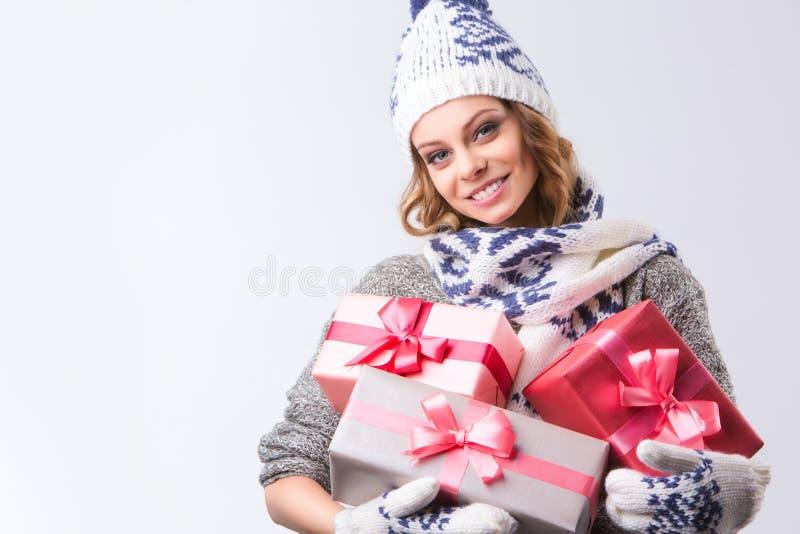 Menina feliz bonita no chapéu e nos mitenes da camiseta com as caixas de presentes do Natal imagens de stock