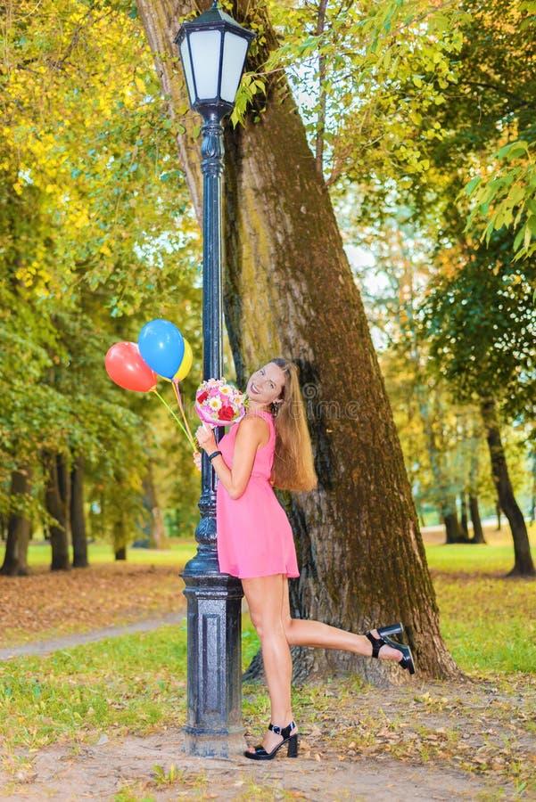 Menina feliz bonita no vestido cor-de-rosa com flores e suportes das bolas perto da lanterna imagens de stock