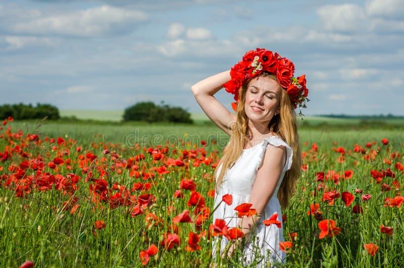 Menina feliz bonita nova com cabelo longo em um vestido branco no campo da papoila com uma grinalda em sua cabeça fotografia de stock royalty free