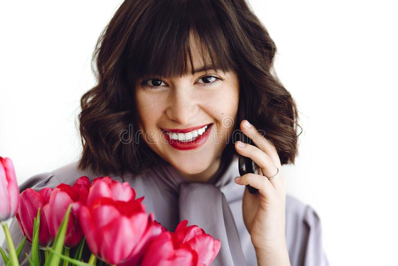 Menina feliz bonita que fala no telefone e no sorriso, guardando tulipas vermelhas no fundo branco dentro, espaço para o texto Jo fotos de stock