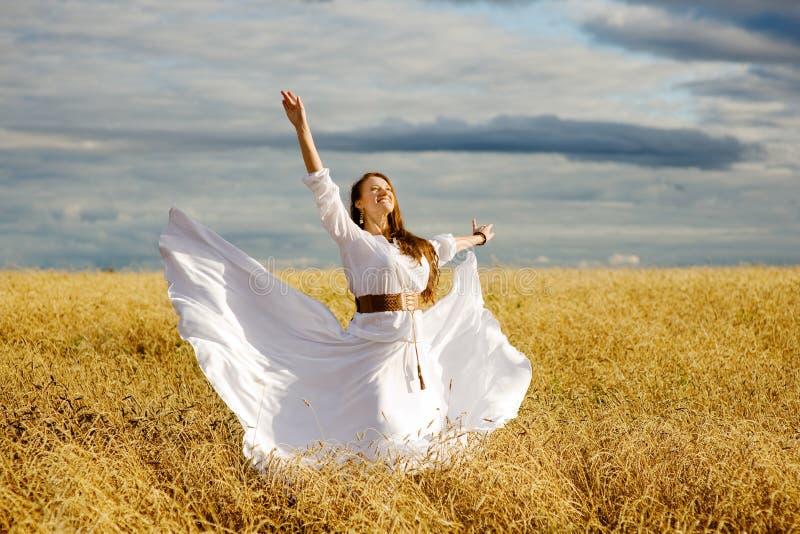 Menina feliz bonita que tem o divertimento no campo de trigo fotos de stock