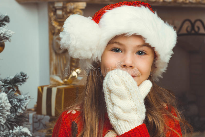 Menina feliz bonito no assento vermelho e em smilling do chapéu fotografia de stock