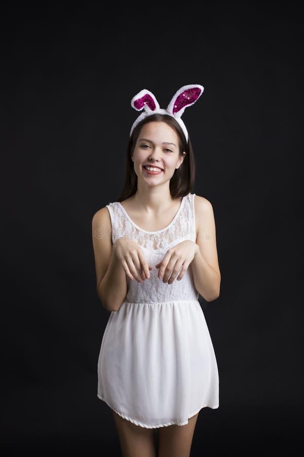 Menina feliz bonito que veste um vestido branco e as orelhas do coelho que guardam caixas de presente O traje do coelho no fundo  imagens de stock royalty free