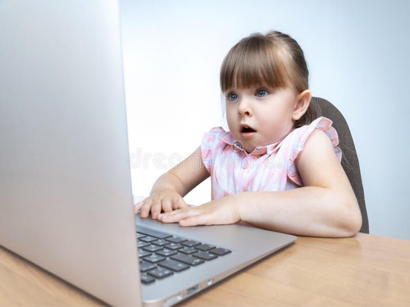 Menina feliz chocada ou surpreendida que usa o computador fotografia de stock