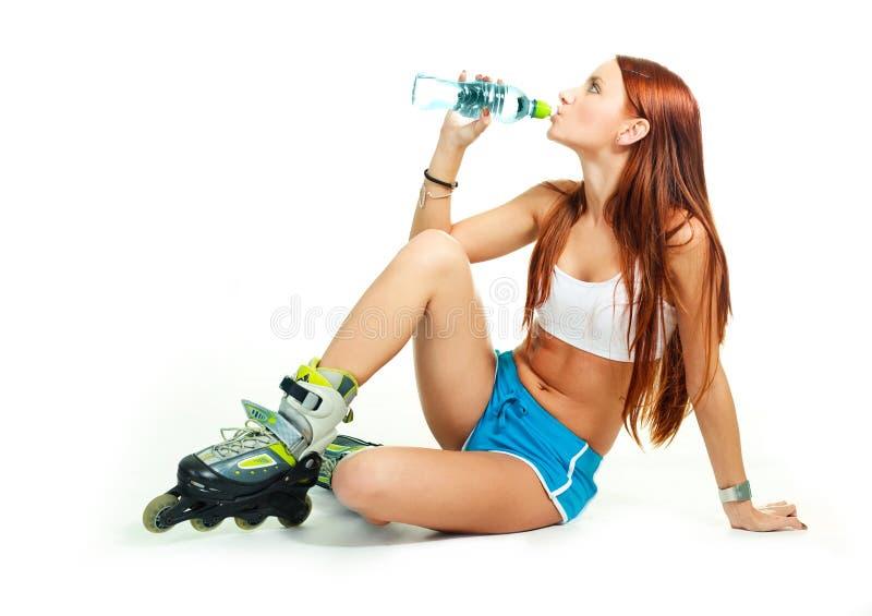 Menina feliz com água bebendo dos rollerskates imagens de stock