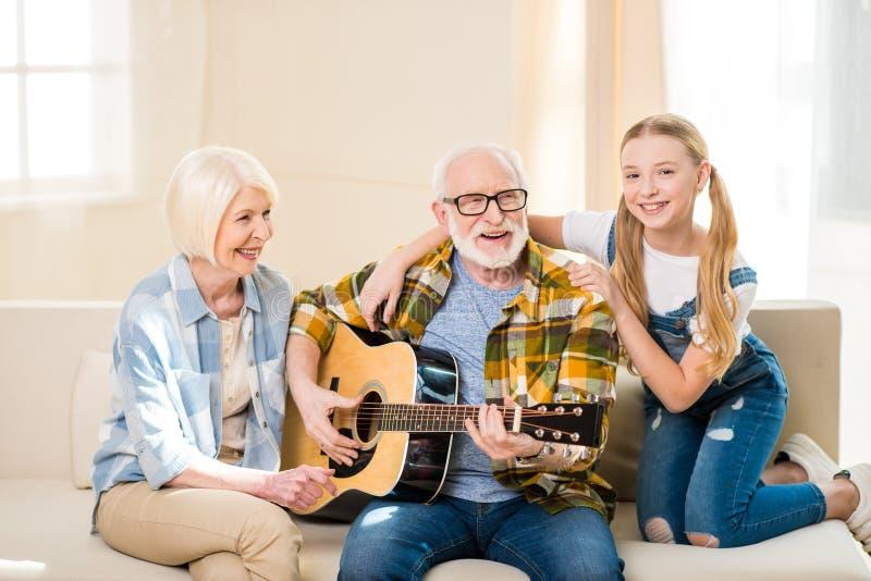 Menina feliz com as avós que sentam-se junto no sofá e que jogam a guitarra acústica fotos de stock