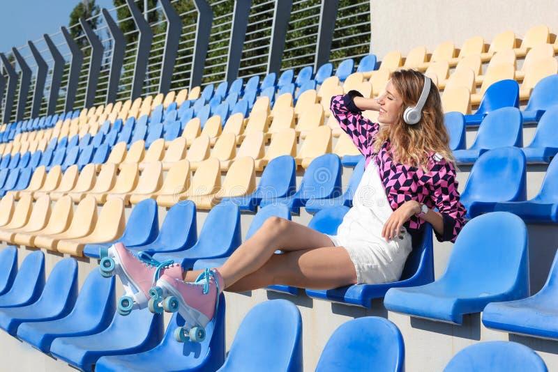 Menina feliz com assento retro dos patins de rolo fotografia de stock