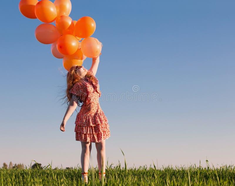 Menina feliz com balões alaranjados fotos de stock royalty free