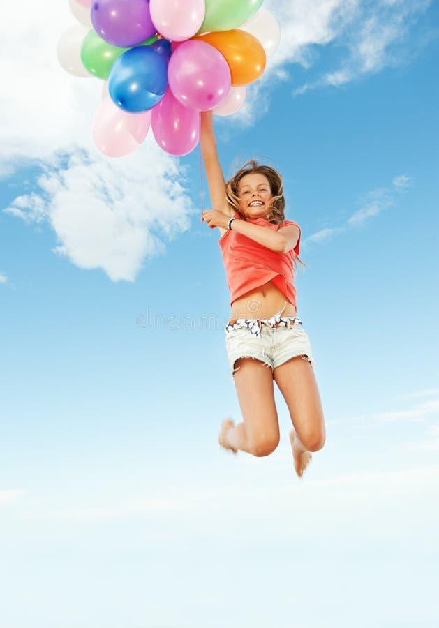 Menina feliz com balões coloridos foto de stock