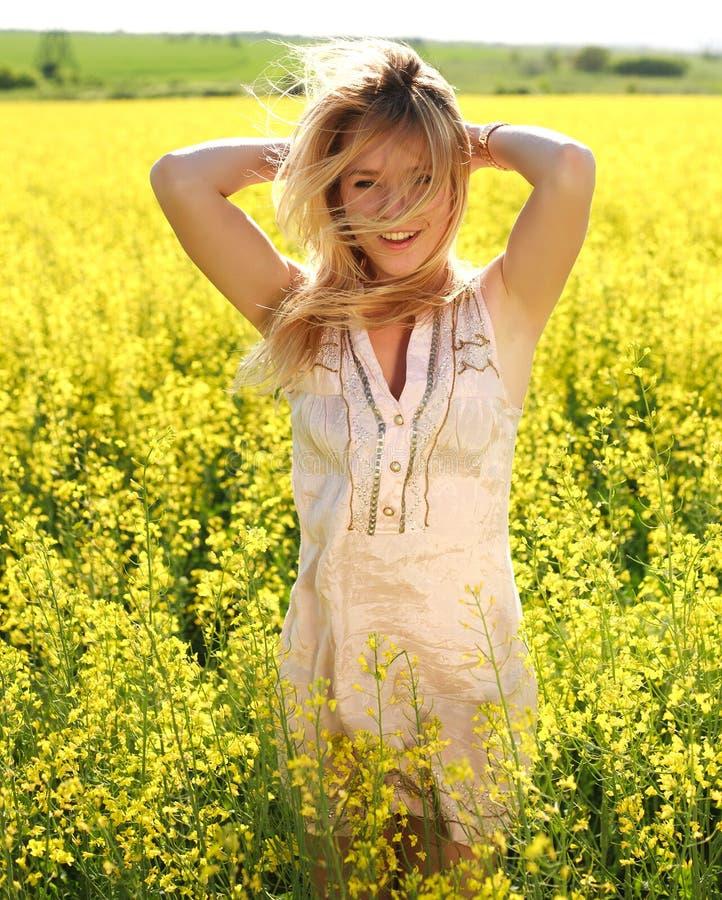 Menina feliz com braços acima, relaxando na primavera o campo amarelo foto de stock royalty free