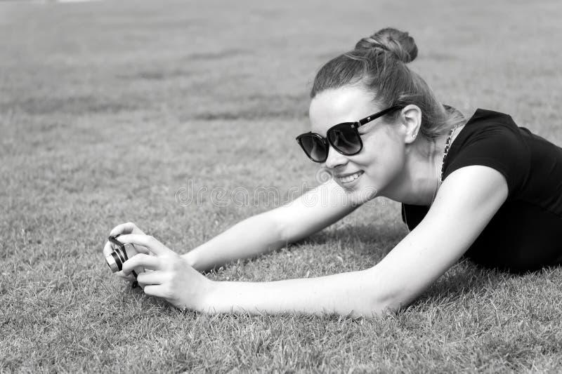 Menina feliz com a câmera na grama verde em Paris, França fotos de stock