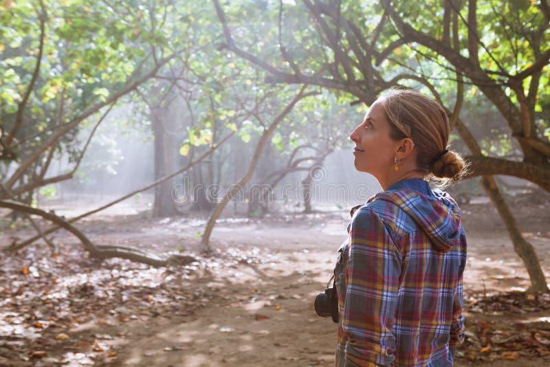 Menina feliz com caminhada da câmera da foto apenas pelo trajeto da selva imagem de stock