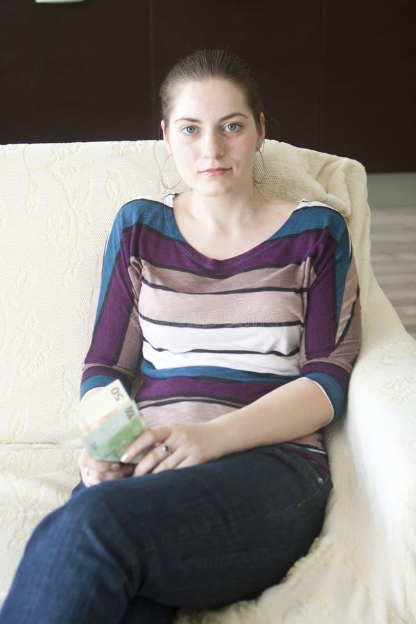 Menina feliz com euro no sofá imagem de stock