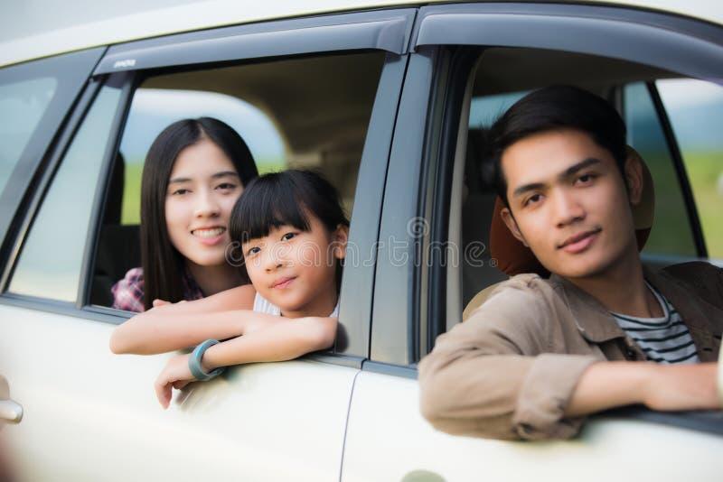 Menina feliz com a família asiática que senta-se no carro para o enjo imagem de stock