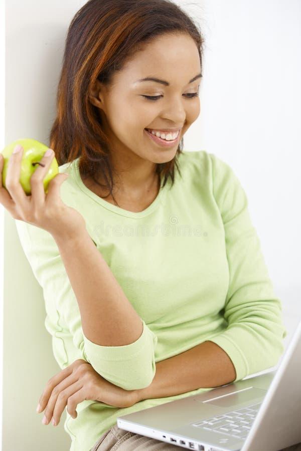 Menina feliz com maçã e portátil fotografia de stock