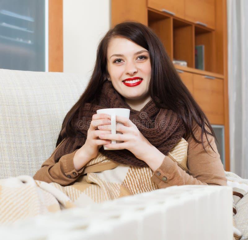 Menina feliz com o copo perto do calefator fotografia de stock