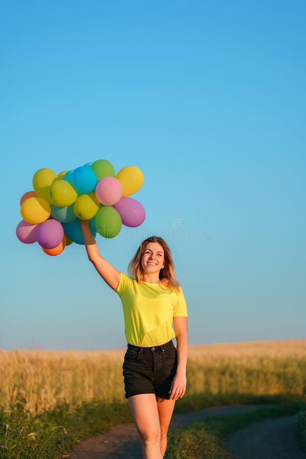 Menina feliz com os balões coloridos contra o céu azul foto de stock royalty free