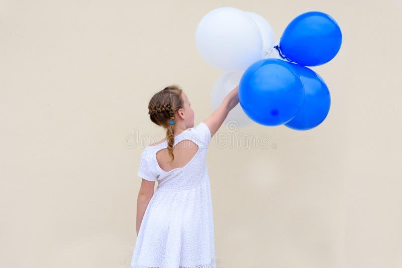 Menina feliz com os bal?es azuis e brancos imagens de stock royalty free