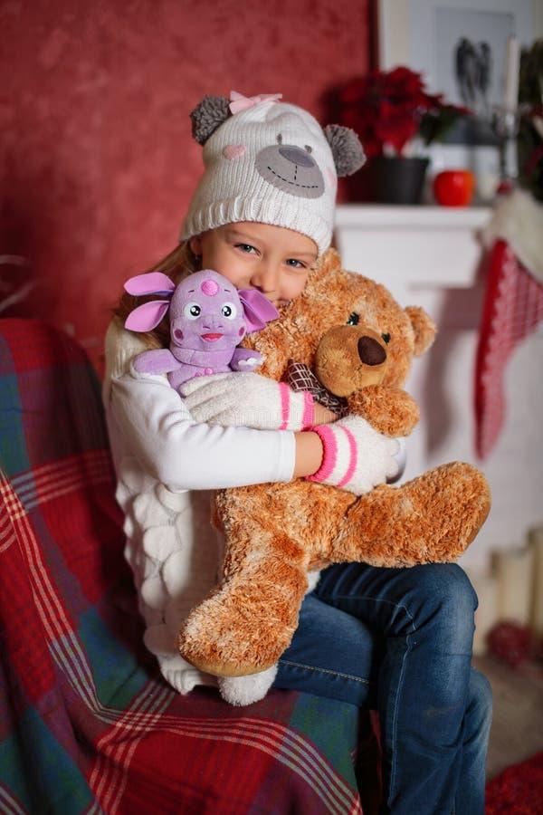 Menina feliz com os brinquedos macios no tempo do Natal imagens de stock