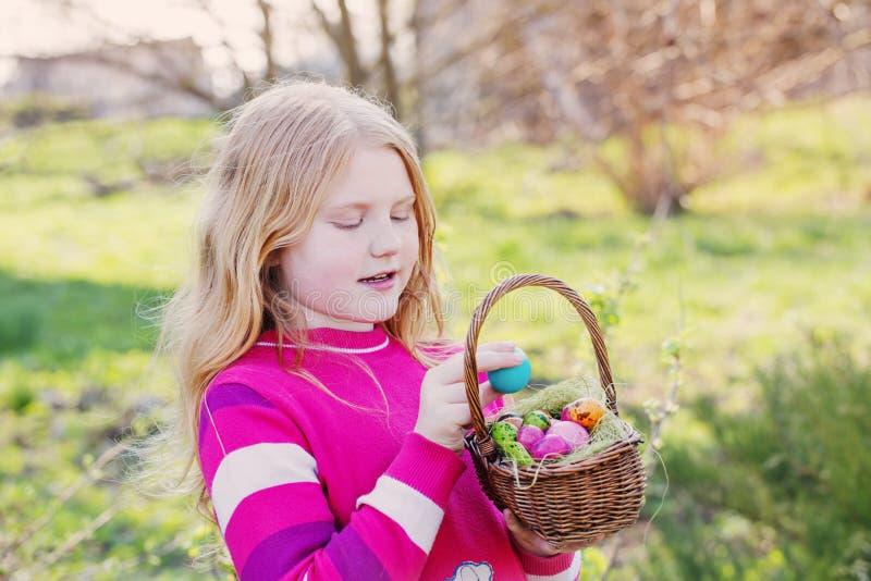 Menina feliz com os ovos da páscoa exteriores imagem de stock