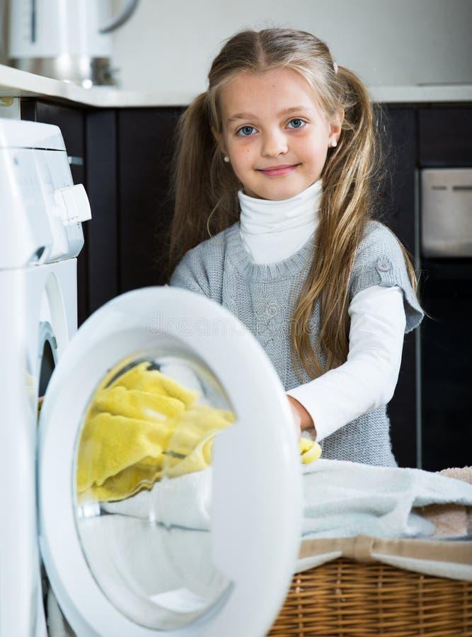Menina feliz com os rabos de cavalo que fazem a lavanderia dentro imagem de stock royalty free