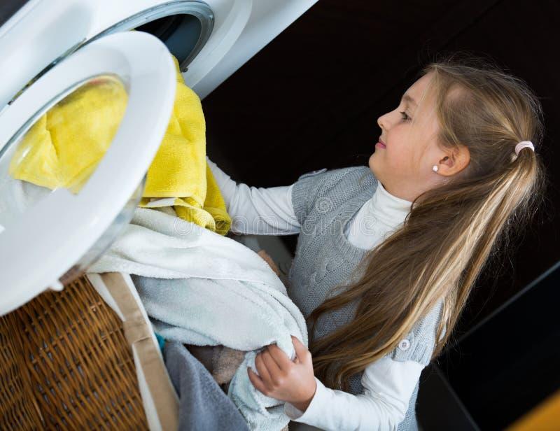 Menina feliz com os rabos de cavalo que fazem a lavanderia dentro imagem de stock