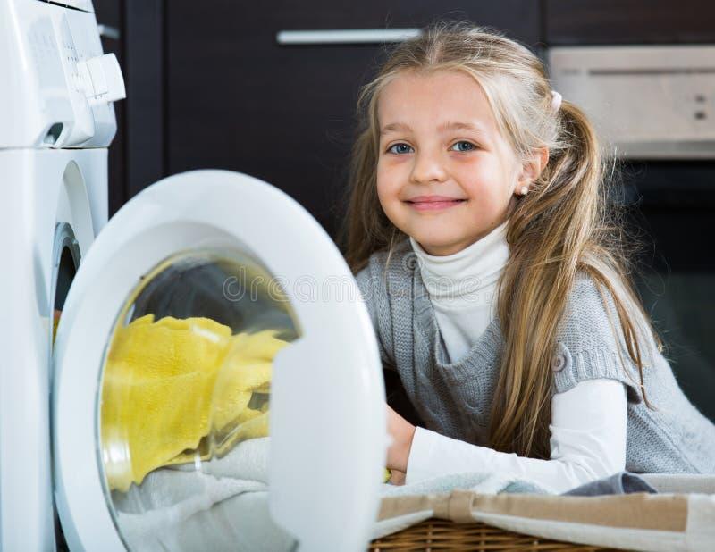 Menina feliz com os rabos de cavalo que fazem a lavanderia dentro fotografia de stock