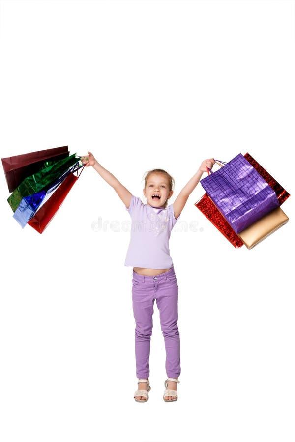 Menina feliz com os sacos de compras que estão no estúdio foto de stock