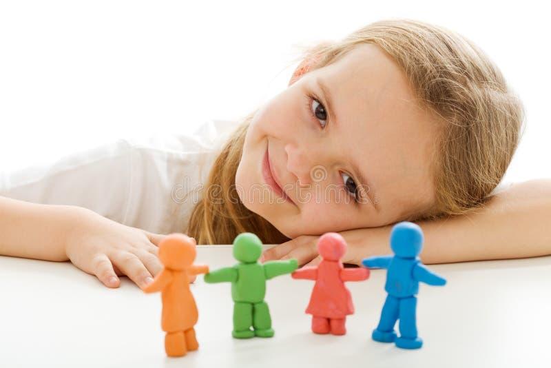 Menina feliz com seus povos coloridos da argila imagem de stock