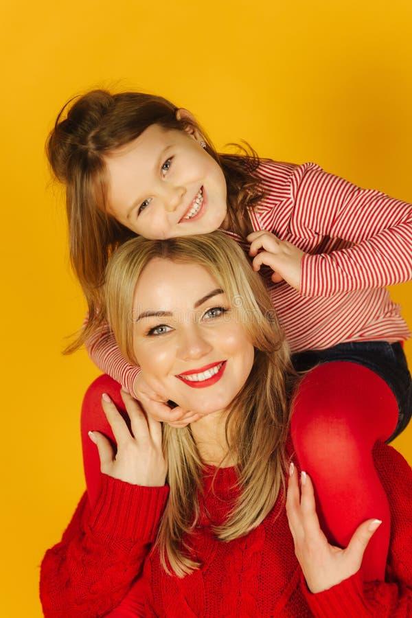 Menina feliz com sua mãe nova no fundo amarelo Filha que senta-se no pescoço da mamã Sorriso foto de stock