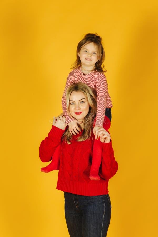 Menina feliz com sua mãe nova no fundo amarelo Filha que senta-se no pescoço da mamã Sorriso imagens de stock royalty free