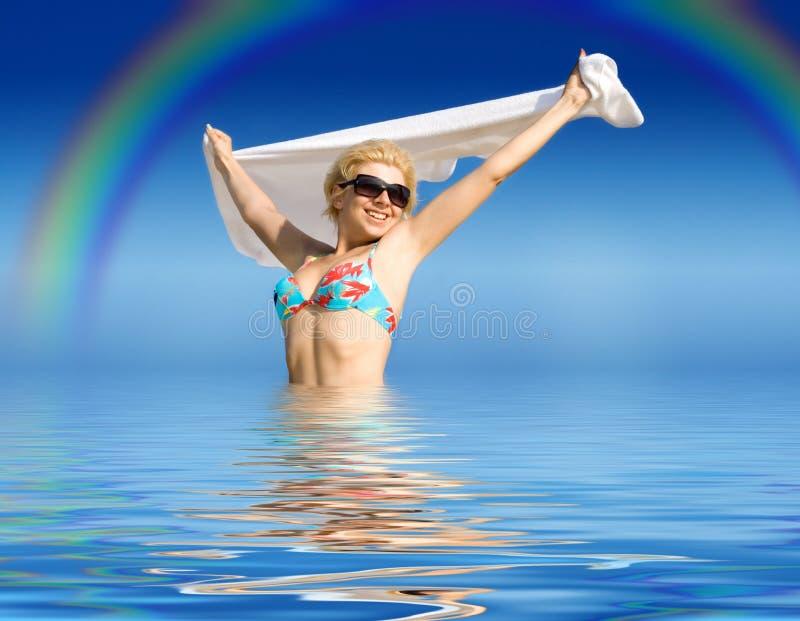Menina feliz com a toalha que está na água imagem de stock