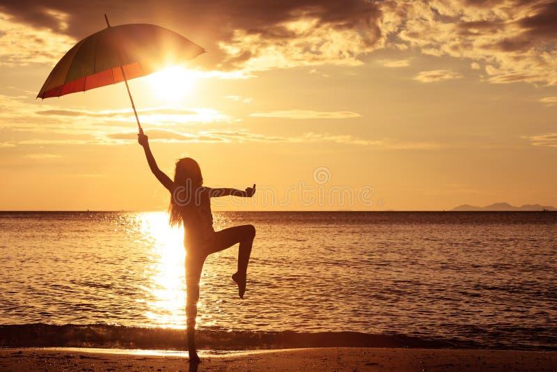 Menina feliz com um guarda-chuva que salta na praia fotografia de stock