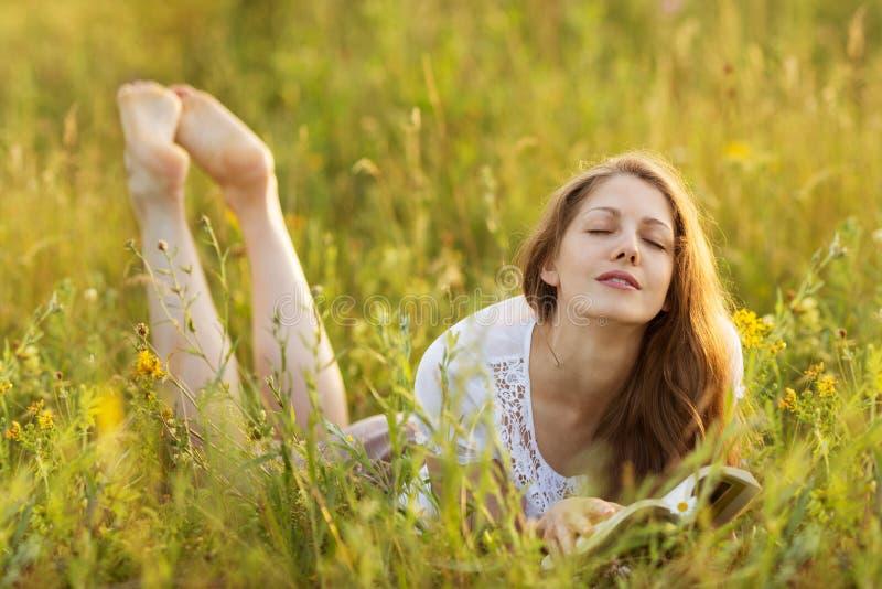 Menina feliz com um livro no sonho da grama imagens de stock royalty free