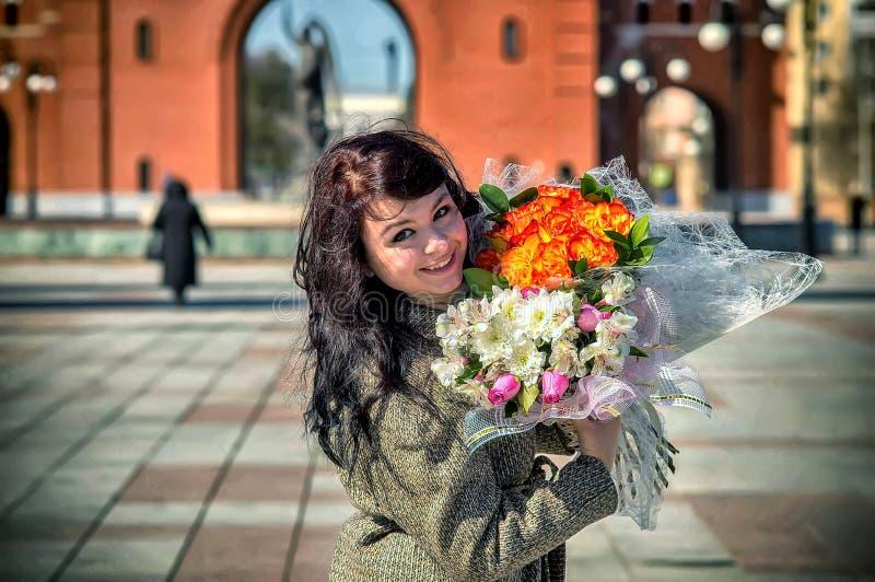Menina feliz com um ramalhete das flores imagens de stock royalty free