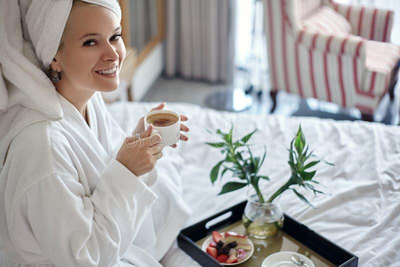 Menina feliz com uma xícara de café Roupão e toalha vestindo da mulher do abrandamento do estilo da casa após o chuveiro Bom dia  fotos de stock royalty free