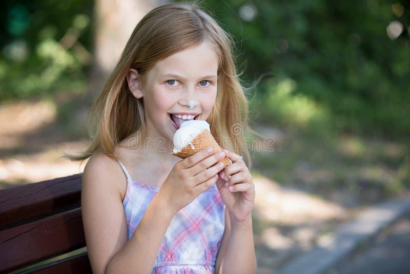 Menina feliz comer o gelado imagem de stock royalty free