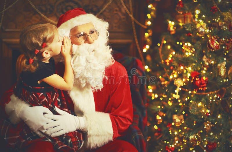 A menina feliz da criança abraça Santa Claus, e diz-lhe secreto foto de stock royalty free
