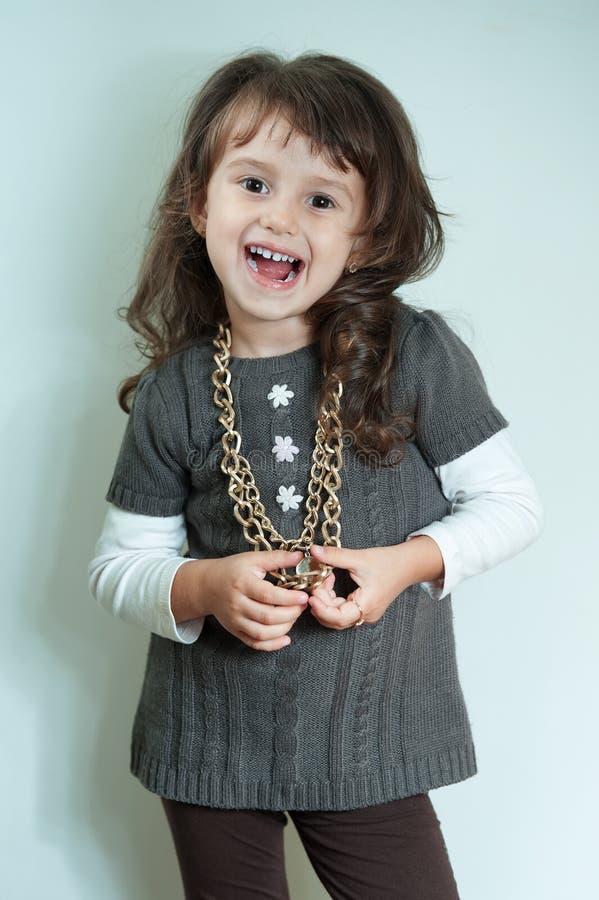 Menina feliz da criança com a corrente do ouro no fundo branco fotos de stock royalty free