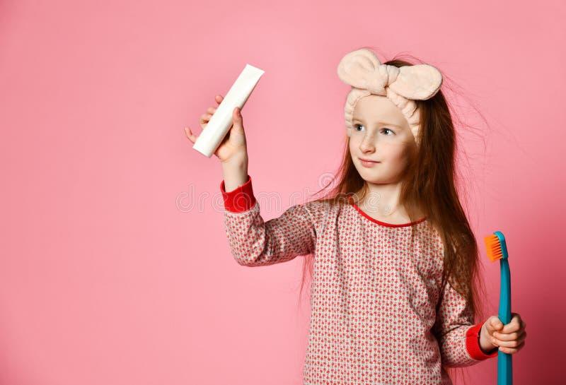 A menina feliz da criança com escova de dentes escova os dentes e os sorrisos fotografia de stock