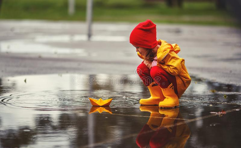 Menina feliz da criança com o barco do guarda-chuva e do papel na poça na imagens de stock royalty free