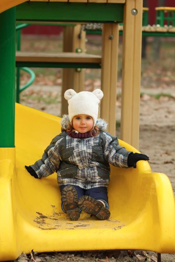 Menina feliz da criança de dois anos que desliza em um campo de jogos do inverno fotos de stock royalty free