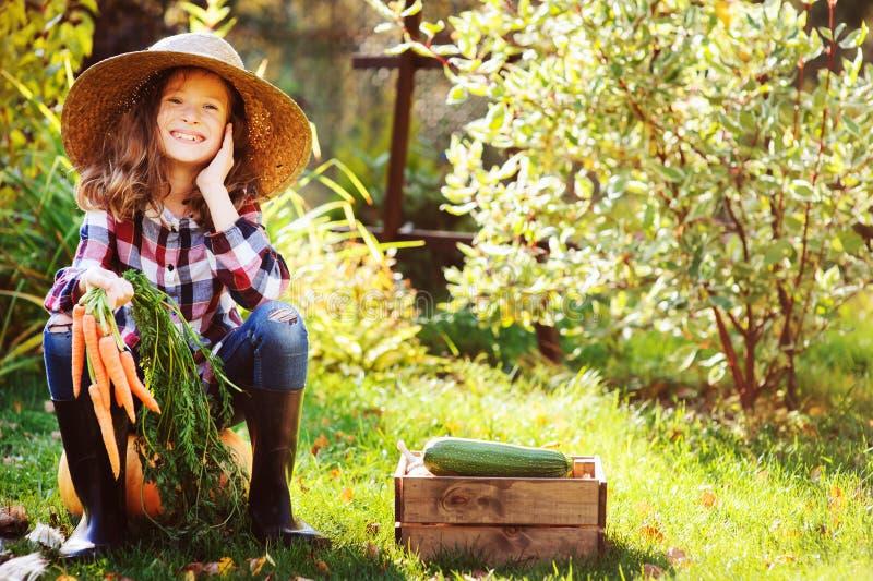 Menina feliz da criança do fazendeiro que senta-se com colheita do outono no jardim foto de stock royalty free
